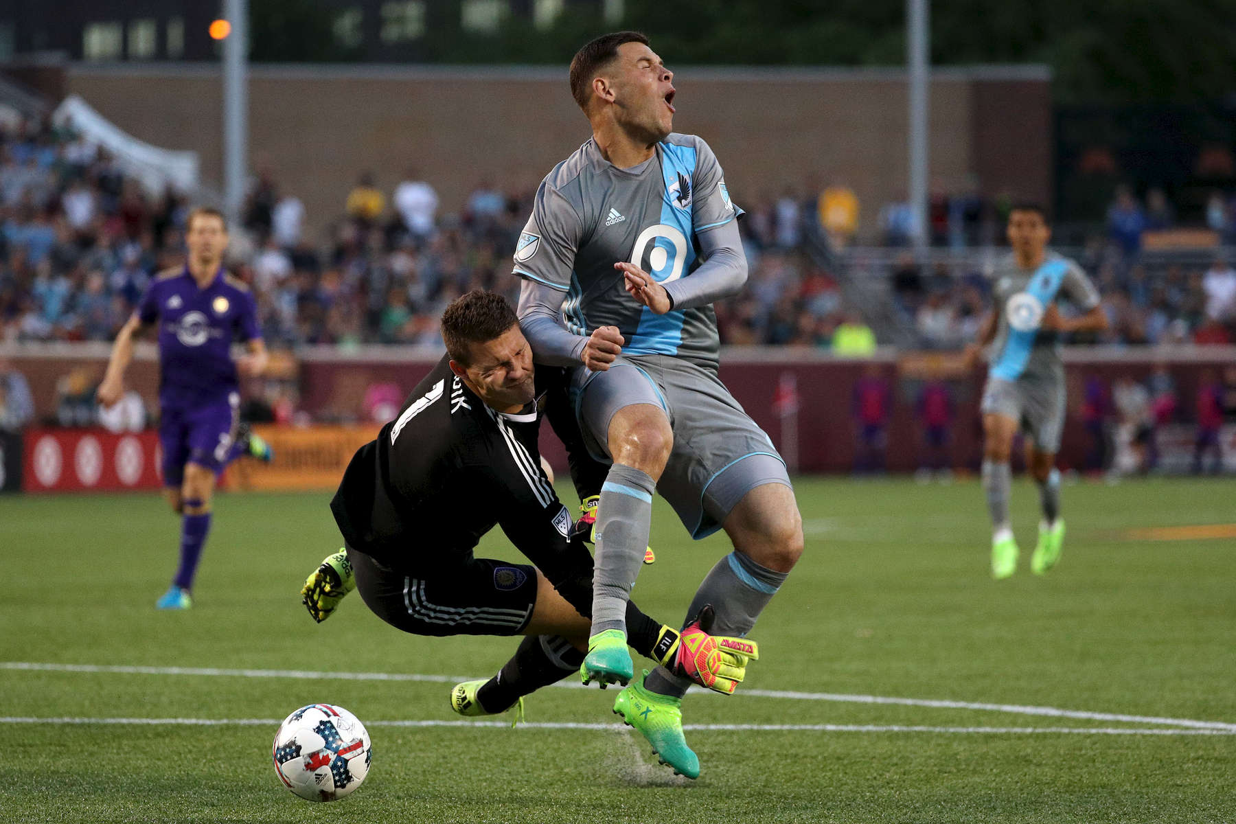 Minnesota United forward Christian Ramirez (21) collides with Orlando City SC goalkeeper Joseph Bendik (1) before taking the ball around him to score during a match at TCF Bank Stadium in Minneapolis.