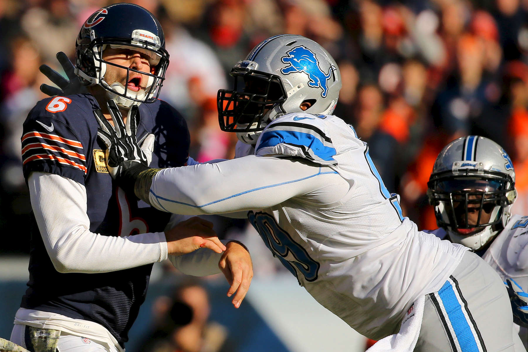 Chicago Bears quarterback Jay Cutler takes a hard hit from Detroit Lions defensive tackle Jermelle Cudjo after completing a pass in the third quarter of a football game between the Chicago Bears and the Detroit Lions at Soldier Field in Chicago.