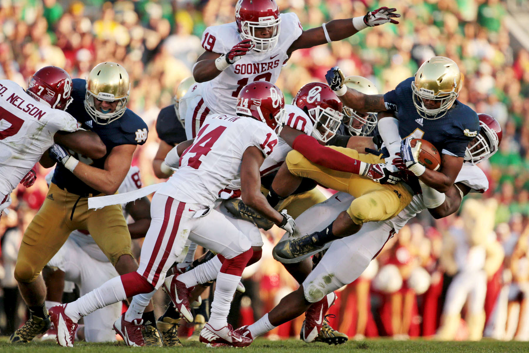 Notre Dame Fighting Irish running back George Atkinson III is pulled down by Oklahoma Sooners defensive end Geneo Grissom as he ran the ball during the second half of an NCAA football game between the Notre Dame Fighting Irish and the Oklahoma Sooners at Notre Dame Stadium in Notre Dame, Ind.