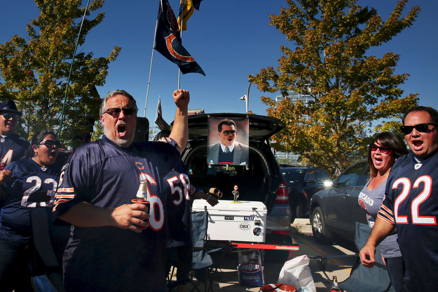Bears fan Marc Sokolowski of Orland Park, at left, leads a cheer with a poster of former Bears coach Mike Ditka in the tailgating area prior to an NFL football game between the Chicago Bears and the Buffalo Bills at Solider Field in Chicago.