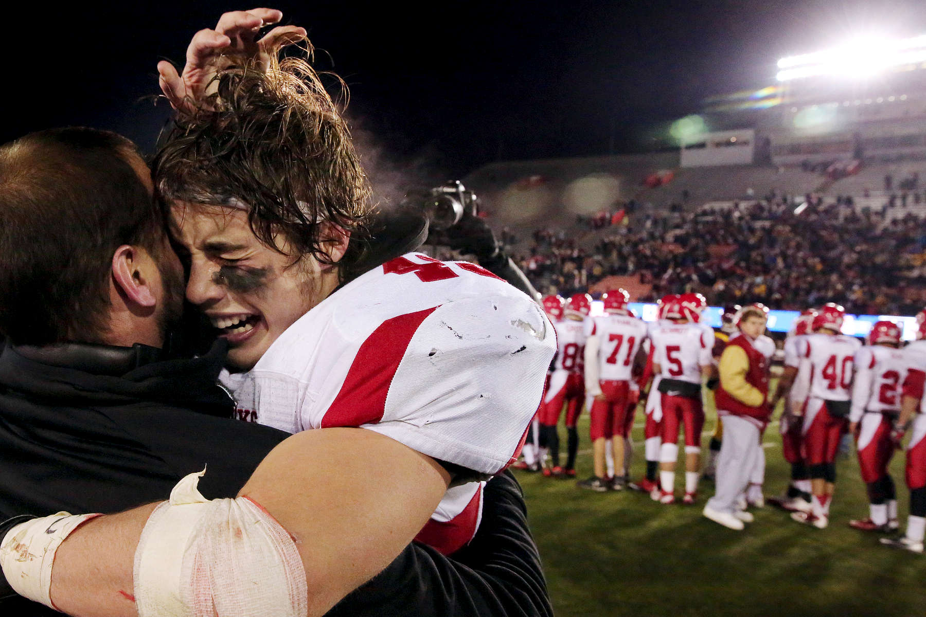 Naperville's Jack Wooldridge gets a hug from his coach after winning an IHSA Class 8A football championship game between the Loyola Academy Ramblers and the Naperville Central Redhawks at Huskie Stadium on the grounds of Northern Illinois University in DeKalb, Ill.