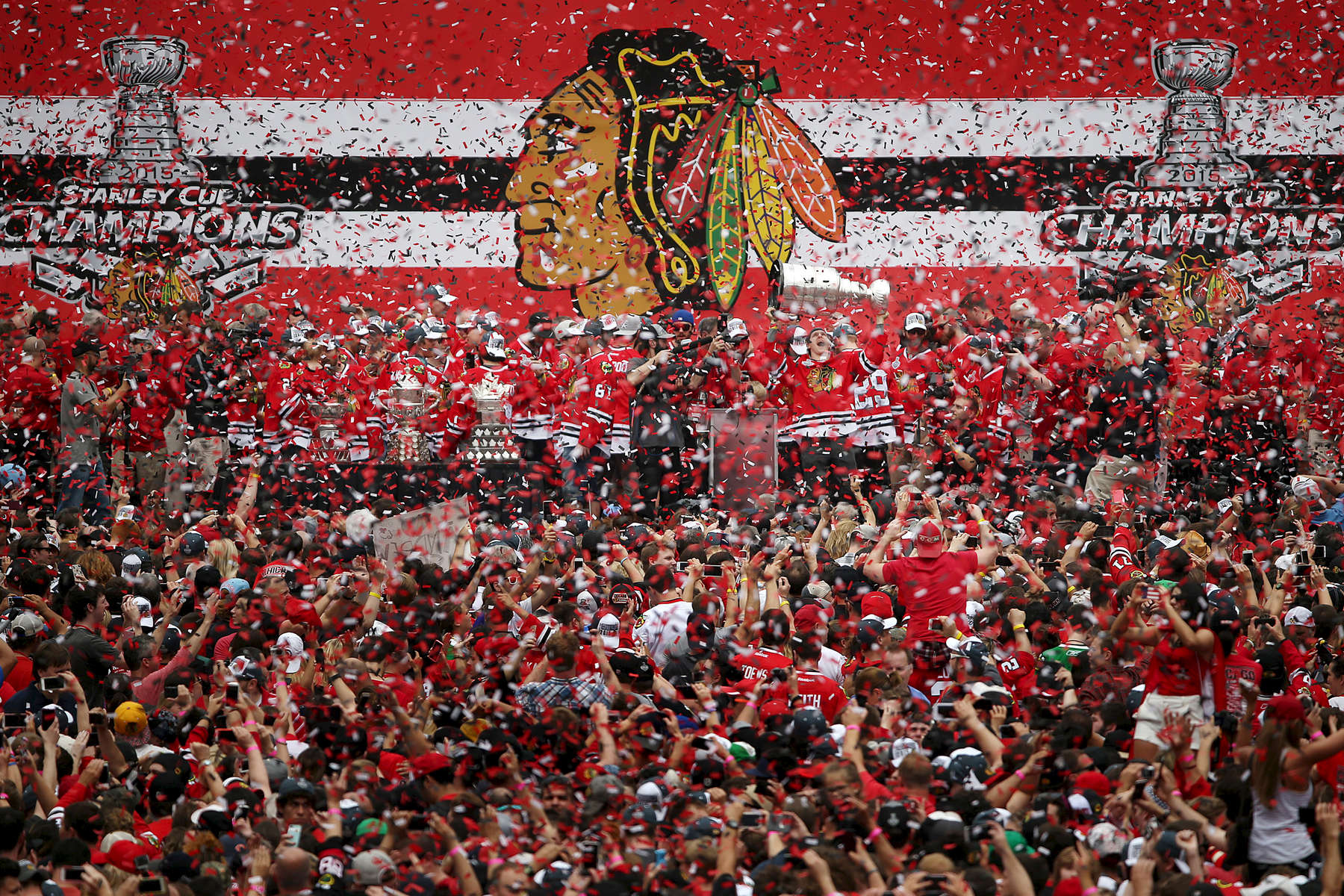 Chicago Blackhawks celebrate with the Stanley Cup trophy as confetti rains down on the crowd of fans during the Blackhawks rally at Soldier Field in Chicago.