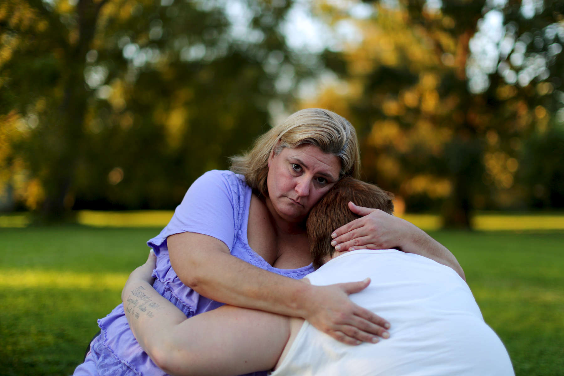 Michele Gans holds her daughter Emma, who was attacked and severely beaten while living at Rover River Academy, as they sit for a portrait at thier home in Galesburg, Ill.