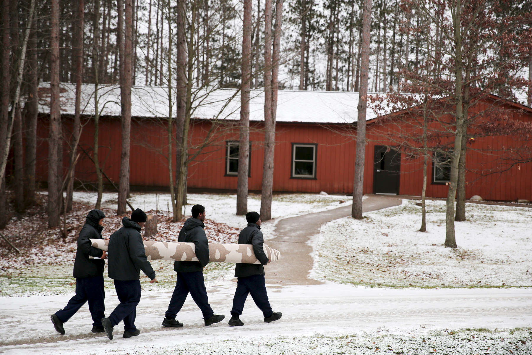 Residents at the Pioneer Work & Learn Center, operated by Wolverine Human Services, carry a rug to be cleaned from their cottage in Vassar, Mich. Court documents show that two staffers testified that they were discouraged from reporting incidents, and fired for contacting officials about trouble.