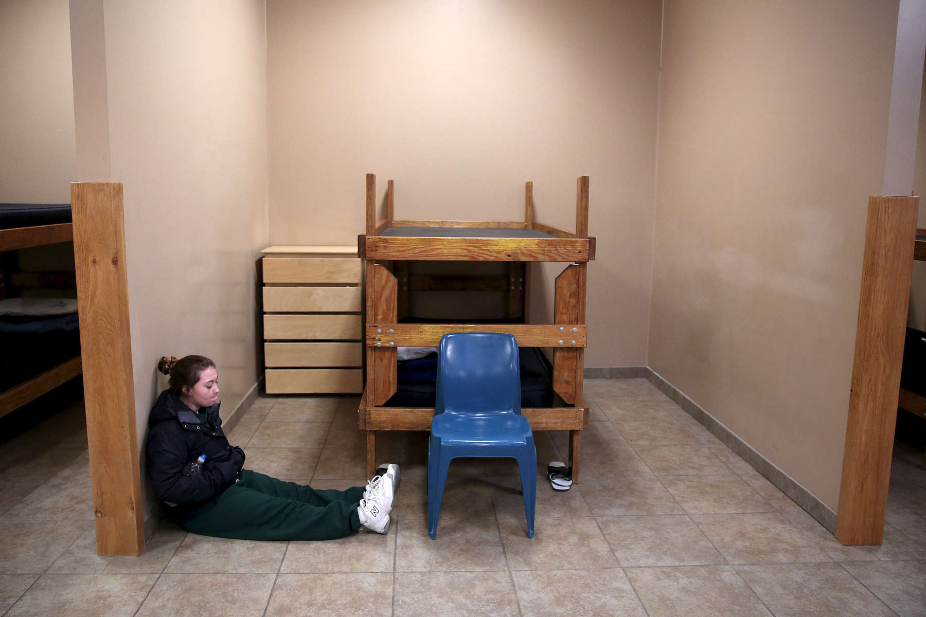 Desiree, 15, a resident at the Pioneer Work & Learn Center operated by Wolverine Human Services sits on the floor near her bed as she waits to be called for lunch in Vassar, Mich.