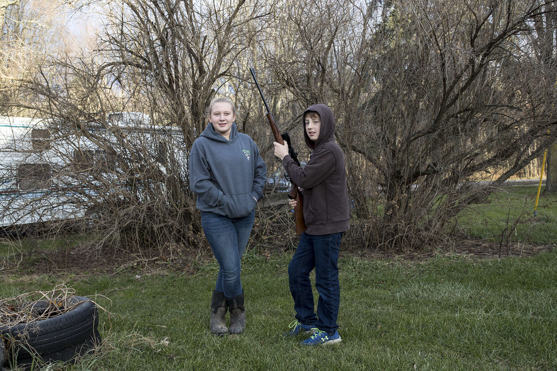 Meredith Cole, age 13, and Ethan Cole, age 11, wait for their father to set up a target in the backyard at their family's dairy farm to practice shooting on the day before the opening of deer rifle hunting season in Troy, Penn., on Sunday, November 26, 2017. Meredith is over the age of 12 and has passed a hunter safety course and is therefore allowed to hunt while carrying her own gun as long as she is in the presence of a licensed adult. Ethan is enrolled in the Mentored Youth Hunting Permit program and can hunt with a licensed adult mentor, but the gun must be carried by the adult and only one gun may be used between the pair.