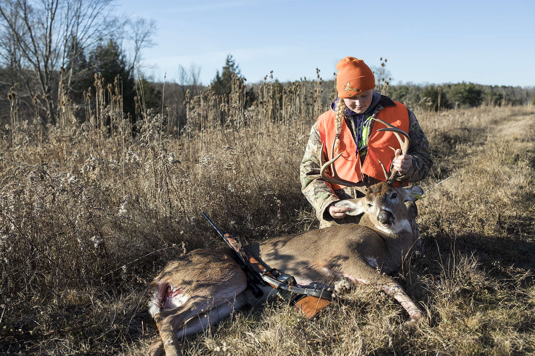 Meredith Cole, age 13, looks at a deer she shot on opening day of deer rifle hunting season in Troy, Penn., on Monday, November 27, 2017. Deer hunting is such an important part of the culture in this part of rural Pennsylvania that the Troy Area School District cancels school the first two days of deer rifle season so children can hunt with their families. Meredith is over the age of 12 and has passed a hunter safety course and is therefore allowed to hunt while carrying her own gun as long as she is in the presence of a licensed adult. She went hunting with her grandfather and was later joined by her brother and father to search for the deer.
