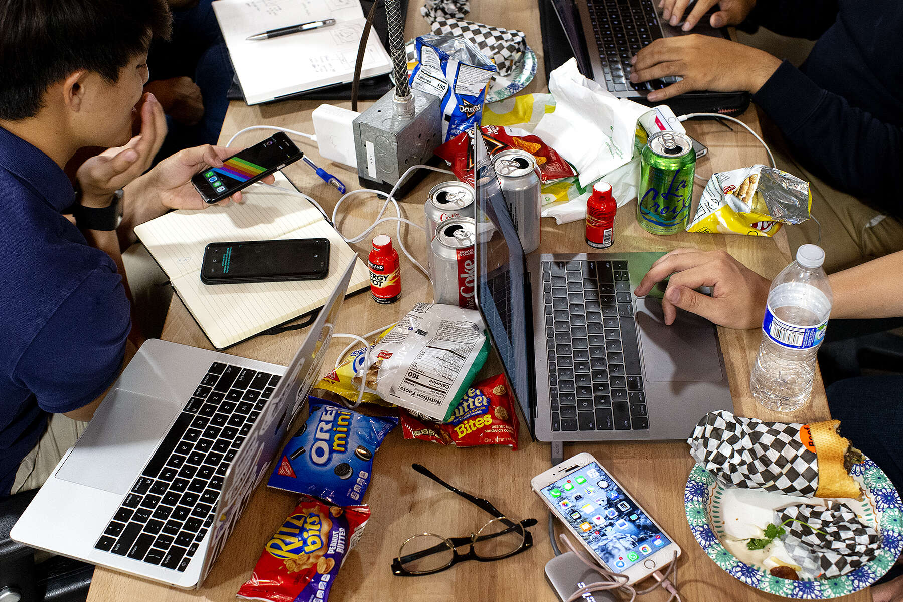 Fueled by snacks, energy drinks, and diet soda, students from Singapore's Nanyang Technological University develop ideas for an augmented reality app during a hackathon in Santa Clara, Calif., on July 27, 2018. Hackathons, an important part of the tech industry eco-system, are events where software developers and other individuals involved in technology development come together to collaborate on teams and create something in a set period of time, often competing for prizes.