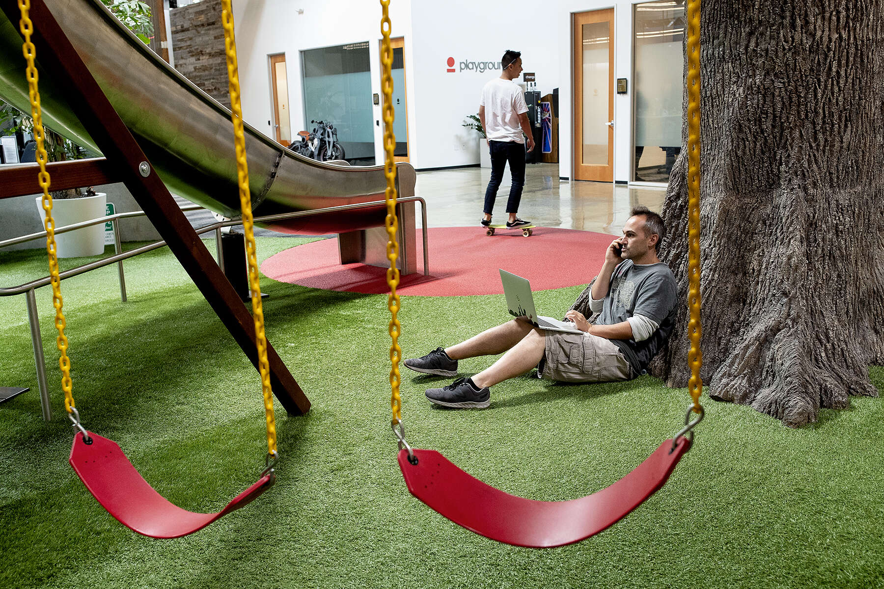 "Joshua Carpentier, an employee at the time at a start-up named Essential, works in the playground area at the offices of technology incubator Playground Global in Palo Alto, Calif., on August 16, 2018. Playground funds and supports start-ups developing new technology, with a focus on artificial intelligence. Carpentier says, ""I always made a point of going down the slide once a day. It was a good reminder to have fun and never take what you do too seriously."""