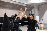 Mo-Sys mechanical engineer Rohan Stent (right) plays virtual reality beach volleyball with Roger Ryder in a booth to demonstrate StarTracker VR by the company Mo-Sys at the Augmented World Expo in Santa Clara, Calif., on June 1, 2018. StarTracker uses reflective stickers that can be stuck to the ceiling or a net while an upwards-looking camera calculates the position of the subject from the stickers. AWS is a large augmented reality and virtual reality conference and expo.