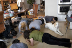Employees of Wefunder gather for an afternoon planking break and are joined by Bucket, a team member's dog, at the company's San Francisco office, a house that is home to the CEO and some employees in San Francisco, Calif., on August 13, 2018. The start-up successfully lobbied Congress to legalize equity crowdfunding, allowing privately held companies to raise investment from everyday people, so-called unaccredited investors.