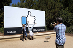 Nicole Voulgaropoulos and her mom, Sheryl Green-Voulgaropoulos, pose in front of Facebook's thumbs-up sign as Mel Voulgaropoulos, her father, photographs them in Menlo Park, Calif., on August 31, 2018. Nicole was at the time a new Facebook employee and her parents had come for a visit. Access to the company's campus is restricted and the sign, the area that welcomes visitors without an employee connection, has become a popular place to sightsee and take photos for people who visit Silicon Valley.