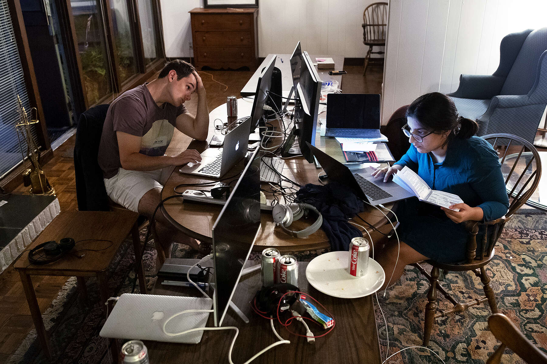 Drew Soldini (left) and Harshita Arora work for Do Not Pay on the beta version of an app to automate 12 big areas of the law at a home in Palo Alto, Calif., on August 15, 2018. Do Not Pay, which originally started as a chatbot to fight parking tickets, is working toward the goal of making the law free for all. The house, their temporary office at the time, is the same home Mark Zuckerberg rented in the summer of 2004 and served as Facebook's headquarters that summer.