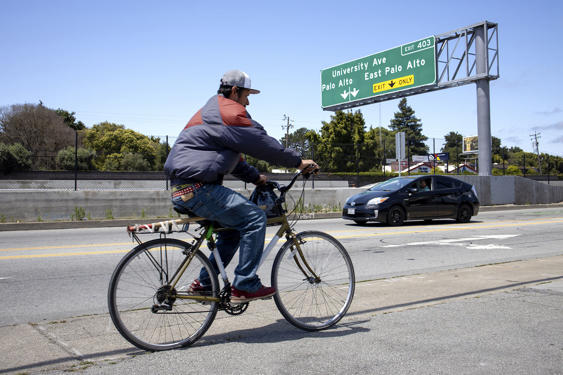 A bicyclist and car move along East Bayshore Road under a Highway 101 sign indicating the exit for University Avenue in East Palo Alto, Calif., on June 16, 2019. While a small sliver of East Palo Alto's land lies on the Palo Alto side of the highway, most of the city is separated by the busy freeway, which creates a physical as well as mental barrier between the two towns.