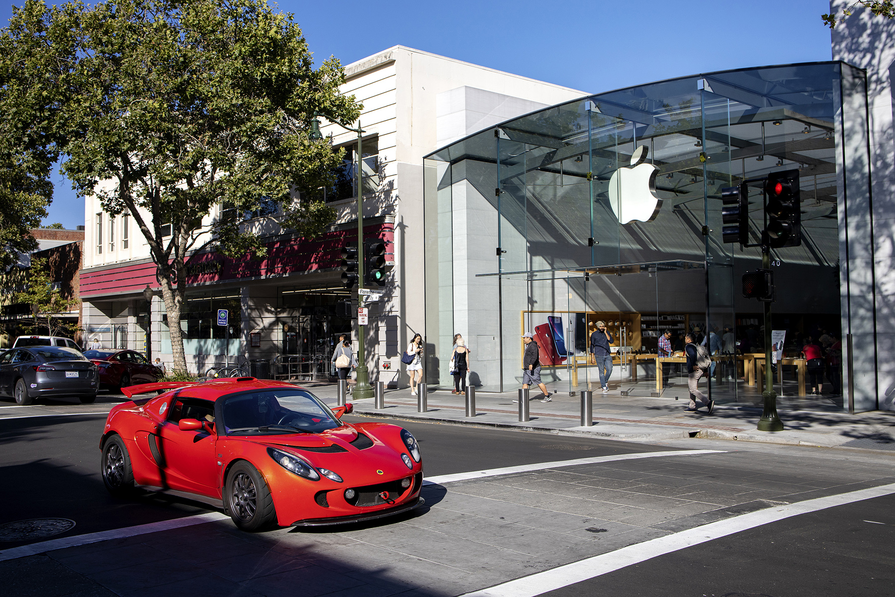 A sports car drives past the Apple Store on University Avenue in an area of downtown that is lined with retail and food establishments in Palo Alto, Calif., on June 7, 2019. Apple co-founder Steve Jobs lived in the town for much of his life. The U.S. Census bureau's most recent figure, in 2012, for retail sales per capita in Palo Alto is $37,083, significantly higher than neighboring East Palo Alto.