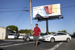 A pedestrian walks under a billboard, visible from Highway 101, advertising Apple products on East Bayshore Road in East Palo Alto, Calif., on Wednesday, June 12, 2019.. East Palo Alto has considerably less retail options than Palo Alto. The U.S. Census bureau's most recent figure, in 2012, for retail sales per capita in East Palo Alto is $9,372, significantly lower than in Palo Alto.