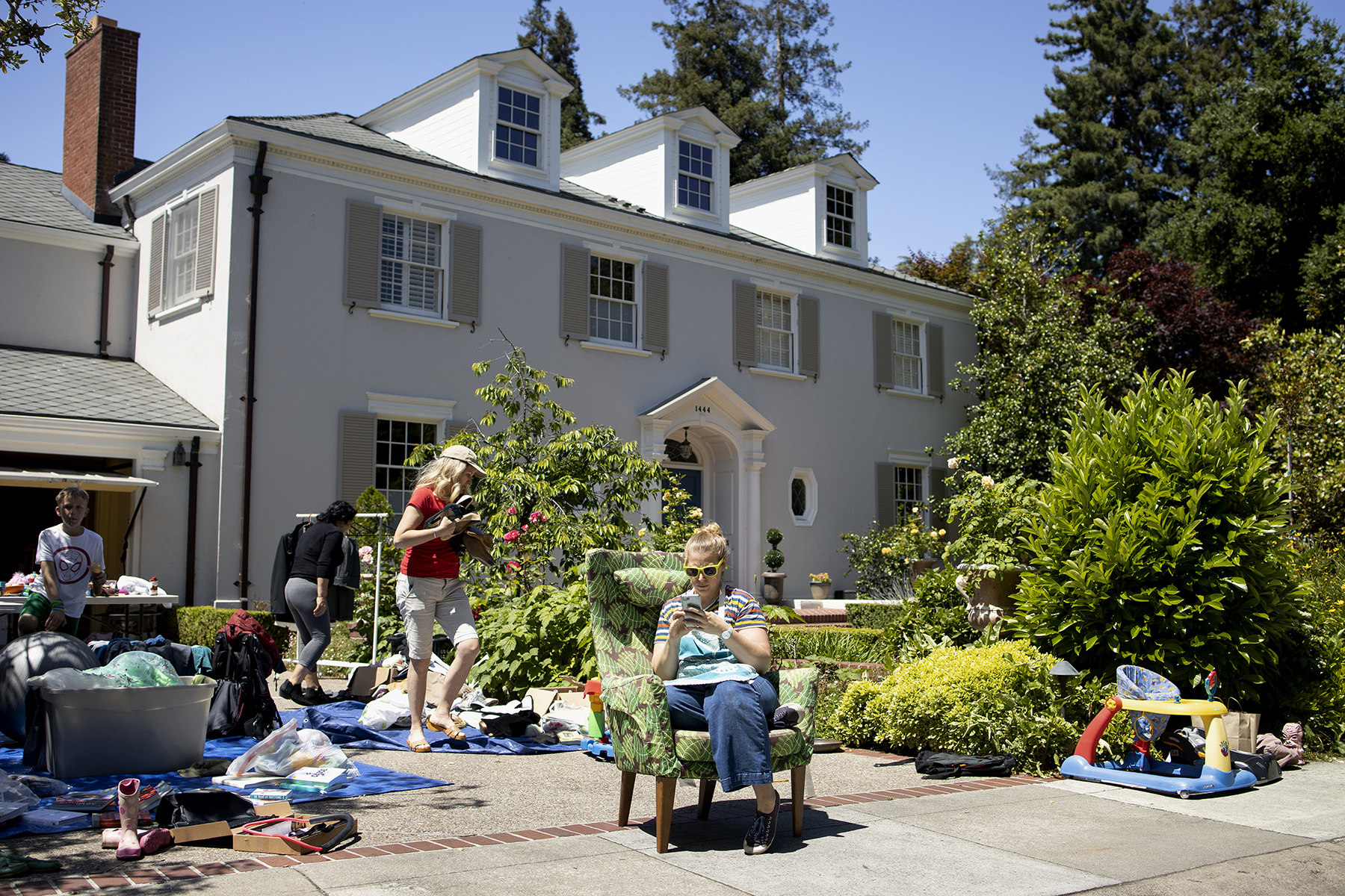 Alice Jacob (center) teams up with her friend Anne Butler (left) to host a garage sale at Butler's house in the Crescent Park neighborhood, where Mark Zuckerberg calls home, in Palo Alto, Calif., on Saturday, May 25, 2019. According to the real estate company Redfin, the median home sales price in Palo Alto is $2,760,000.