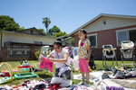 Sandra Martinez shops at a garage sale with her daughter at the home of the Jimenez family in East Palo Alto, Calif., on Saturday June 8, 2019. According to the real estate company Redfin, the medium home sale price in East Palo Alto is an estimated $962,000, almost 2 million less than neighboring Palo Alto.