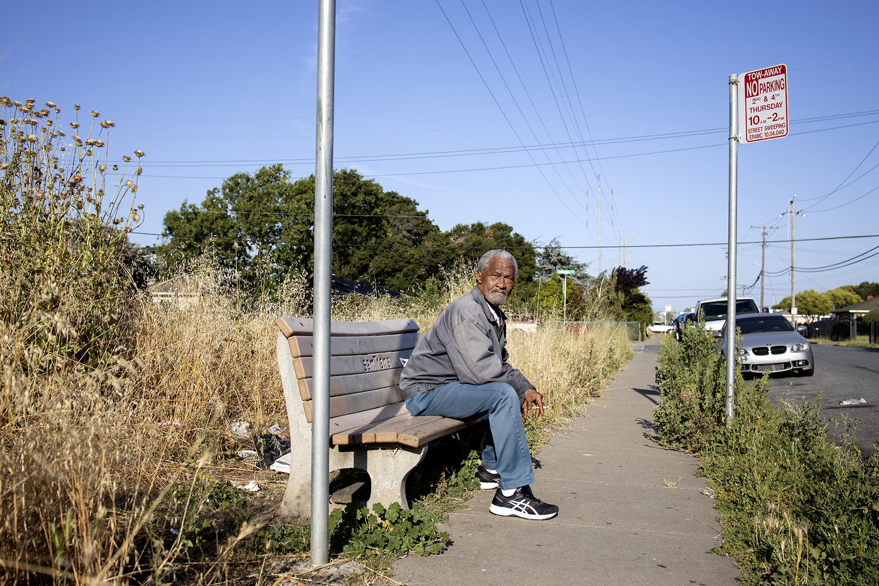 Richard White waits for a bus to take him to Palo Alto to catch the Caltrain to go to work at the corner of Purdue Avenue and Fordham Street in East Palo Alto, Calif., on June 12, 2019. White works as a custodian at SFO Airport.