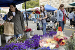 Shoppers peruse a flower stall at the large and bustling California Avenue Famers Market, which is held on Sundays year-round, in Palo Alto, Calif., on May, 26, 2019. Palo Alto also has a Saturday farmer's market downtown.