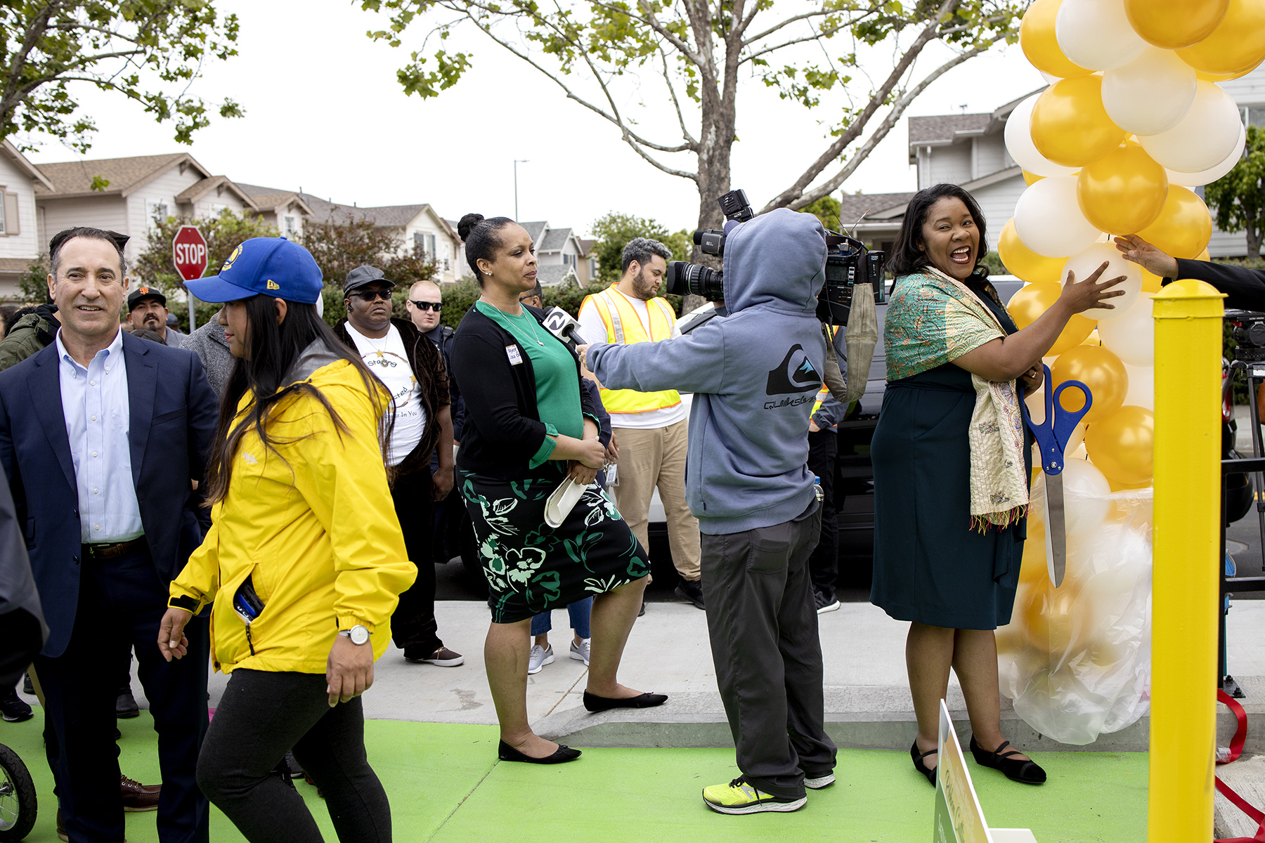 Mayor Lisa Gauthier (center) is interviewed as Vice Mayor Regina Wallace-Jones (right) holds back balloons at a ribbon-cutting ceremony for a new Highway 101 overpass in East Palo Alto, Calif., on May 18, 2019. The overpass connects the two sides of East Palo Alto that have been historically divided by Highway 101. Previously the only crossing for bikes and pedestrians was a small, narrow sidewalk on the busy University Avenue.