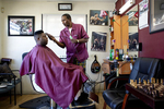 Gregory Smith cuts a customer's hair at Gregory's Enterprise & Barber Shop in East Palo Alto, Calf., on June 26, 2019. Wanting to own his own business, he went to barber school at age 49.