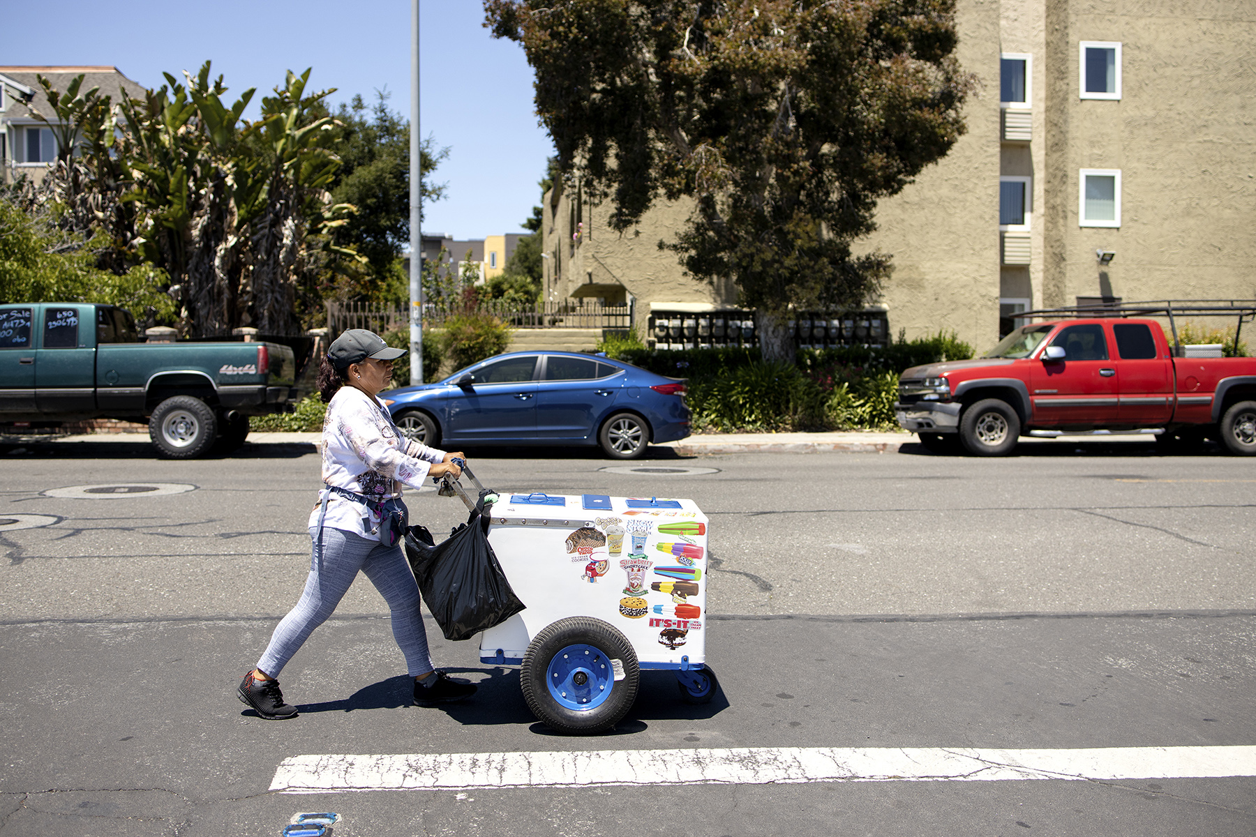 An ice cream and popsicle vendor walks through the city to sell her products on a hot summer day in East Palo Alto, Calif., on June, 2, 2019.