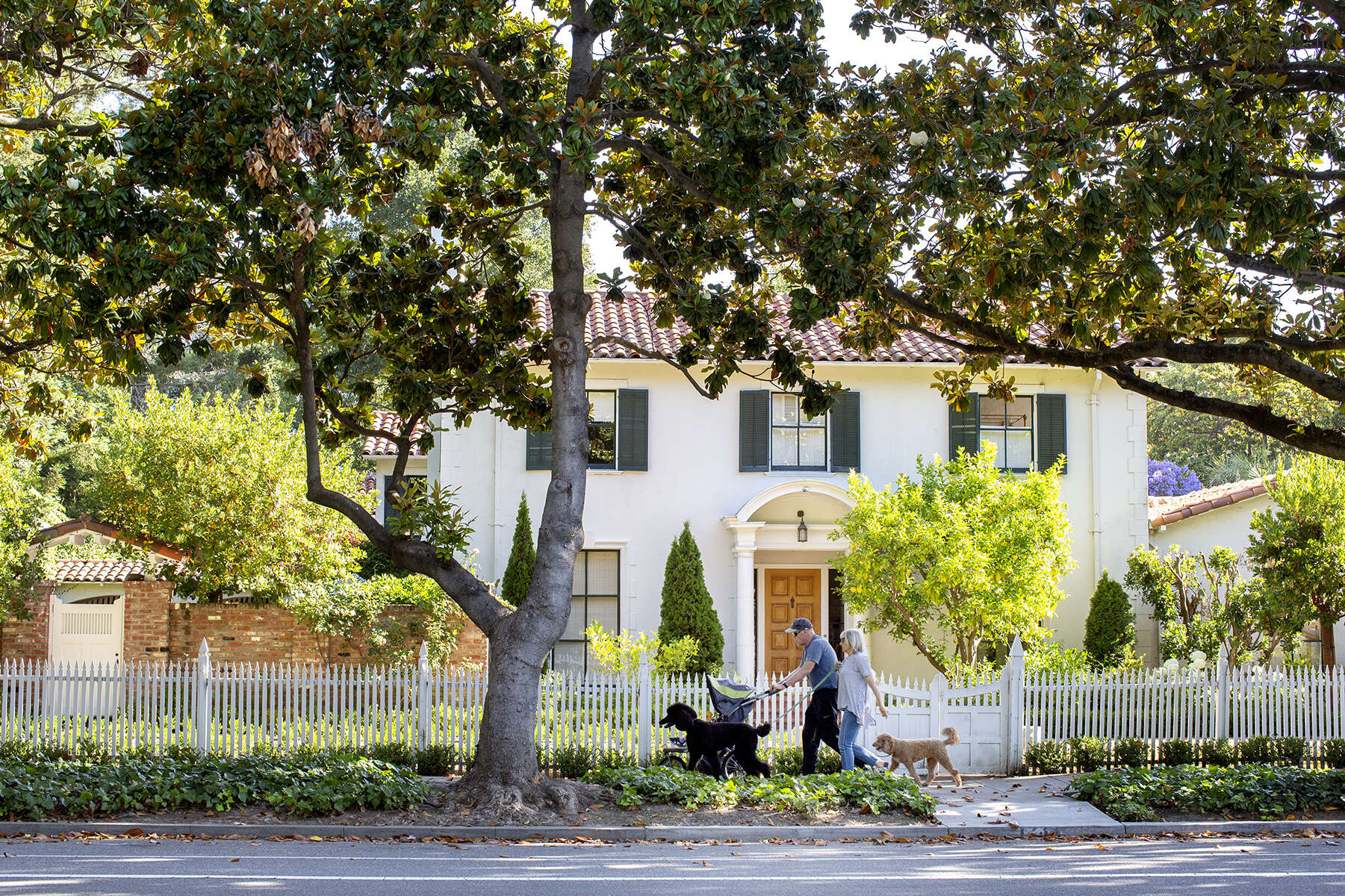 Pedestrians and their dogs walk by a house on the 1200 block of University Avenue in Palo Alto, Calif., on June 23, 2019. The medium home value in the city is an estimated $2,775,164 according to the real estate company Zillow.