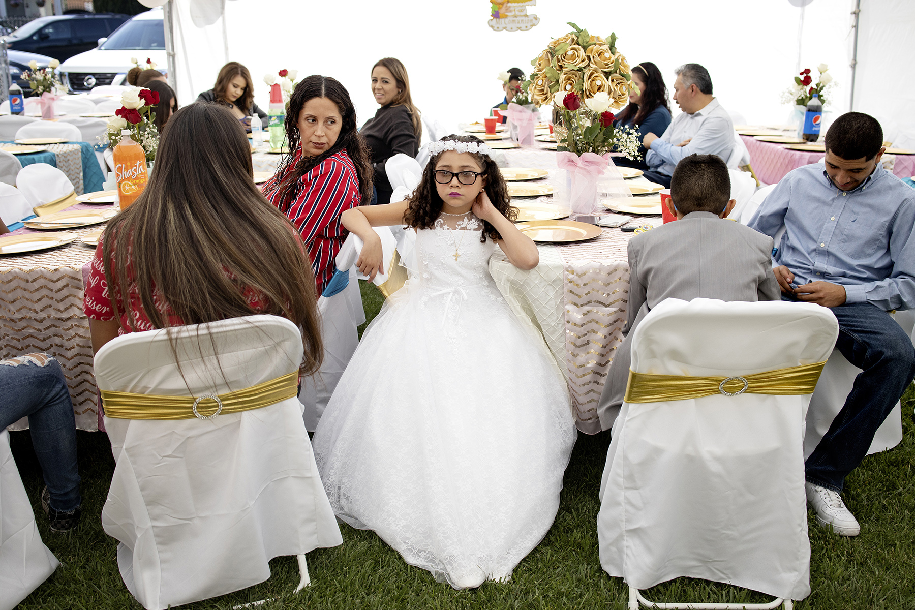 Wendy Figueroa rests with relatives during her first communion party, which she shared with her brother Denis, in a tent in her family's driveway, in East Palo Alto, Calif., on  May 4, 2019. East Palo Alto, located in Silicon Valley, has a strong and close-knit Latino community with an estimated 63.2% of the population identifying as Latino according to the U.S. Census Bureau.