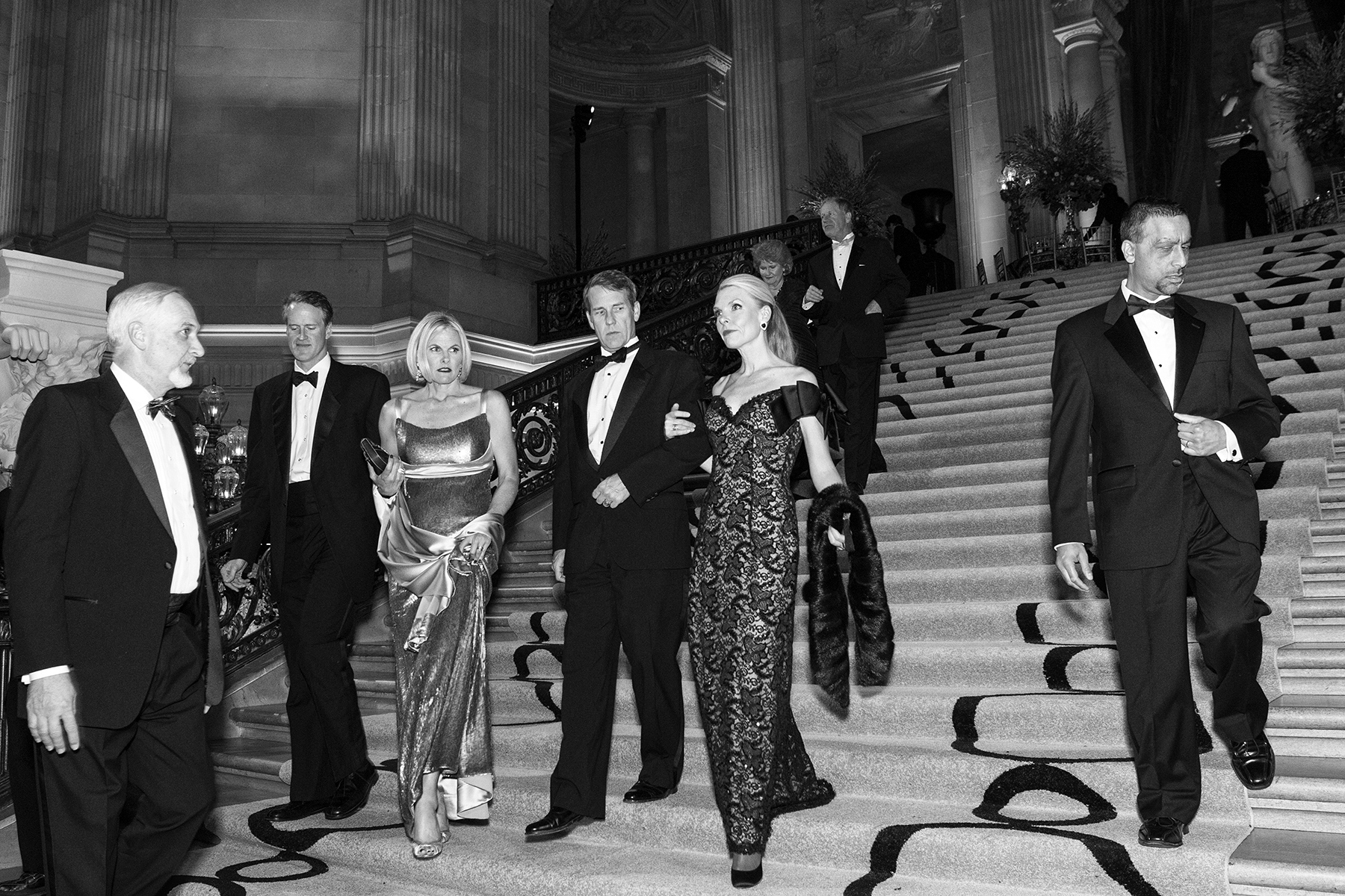 Guests of the San Francisco Ballet Opening Night Gala descend the stairs of City Hall while making their way from dinner to the performance in San Francisco, Calif., on Thursday, January 19, 2012. The galas are often all night affairs consisting of a cocktail hour, dinner, performance and an after party. These elaborate events give participants a chance to dress up, mingle with one another and generally see and be seen.       This photograph is of a candid moment and was not directed in any way.