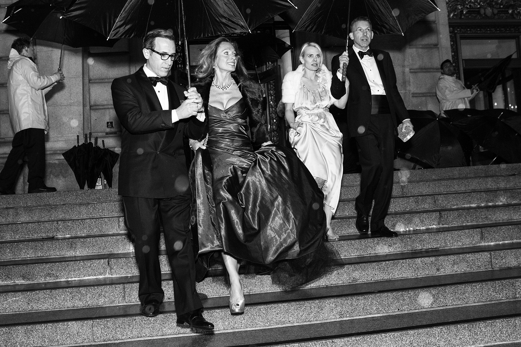 Alan Malouf (left) helps his friend Elisabeth Thieriot keep her gown dry while moving from dinner to the performance during a rainstorm at the San Francisco Ballet Opening Night Gala in San Francisco, Calif., on Thursday, January 19, 2012.This photograph is of a candid moment and was not directed in any way.