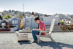 Guillaume Lachaud, an android engineer who builds mobile apps for Uber, works on the roof of 20 Mission, a co-living house where he was living at the time, in San Francisco, California in March 2015. Around 45 people live in the building, which is a former single room occupancy hotel that had been vacant for several years before housing the co-living community, which includes many start-up entrepreneurs. Lachaud, originally from France, is one of many young people from all over the world who have come to San Francisco to participate in the economic boom in the technology industry.