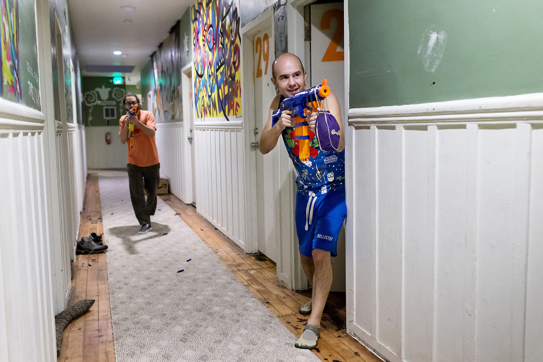 Andrew Ward, right, and Chris Cassano battle their fellow housemates with Nerf guns during an organized Nerf gun battle at 20 Mission, a co-living house in the Mission District, in San Francisco, California in July 2015. The community is home to around 45 people, many of whom are entrepreneurs. Many of the residents are close friends and impromptu gatherings and more formal parties are commonplace at the community.