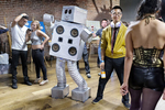"""Chris Hirst entertains guests in his """"Robot Dance Party"""" costume during a party organized by the co-living house 20 Mission, home to many start-up entrepreneurs, titled """"Too Big for Our House"""" in San Francisco, Calif., in July 2015. The house's elaborate parties had been getting almost too large for their living space so they decided to rent a venue downtown to host the event. Hirst wears his robot suit, which has speakers built into it, to DJ events and parties around town."""