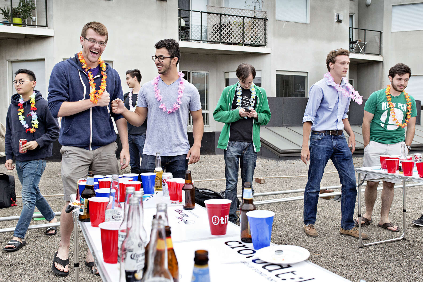 Allen Kleiner (left) and Jonathan Osacky congratulate each other while playing beer pong during a happy hour party at the office of the now defunct crowdfunding start-up Tilt in July 2015. The happy hour was a fundraiser for the organization Girls Who Code and guests were asked to make a donation through the company's website to gain entrance to the event.
