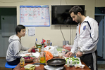 Lior Neu-ner (right) cooks while his housemate Darren Lee eats dinner in the communal kitchen at 20 Mission, a co-living house, in San Francisco, Calif., on Monday, March 23, 2015. Around 45 people live in the building, which is a former single room occupancy hotel that had been vacant for several years before being turned into the co-living space. Many of the residents are start-up entrepreneurs and the community is a mix of temporary occupants with people who have made the space their home on a more long-term basis. Neu-ner was living at 20 Mission for a few months while in San Francisco to participate in a start-up accelerator with his parking app Parko and Lee lived in the house temporarily while transitioning to the city.