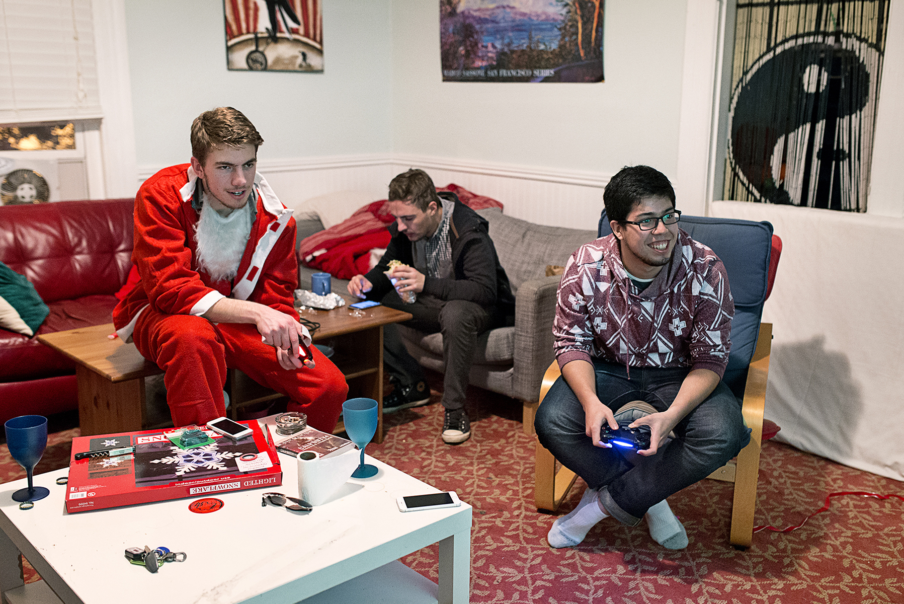 Sean Ross (left) plays video games with his housemate Bastian Ermann while hanging out in the common room at 20 Mission with Henri Roussez (center) in San Francisco, Calif., on Saturday, December 13, 2014. The co-living house is home to around 45 people, many of whom are entrepreneurs or working in the tech industry. Most of the residents have their own room, but share the common room, one kitchen and two bathrooms.