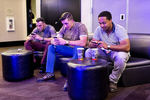Danny Lizotte, Tim Lizotte and Colton Walker, seem left to right, check their phones while attending the Startup and Tech Mixer in support of a friend who was launching a job app at the event in San Francisco, California in August 2014. The networking event was for a time held once every few months and drew hundreds of attendees.