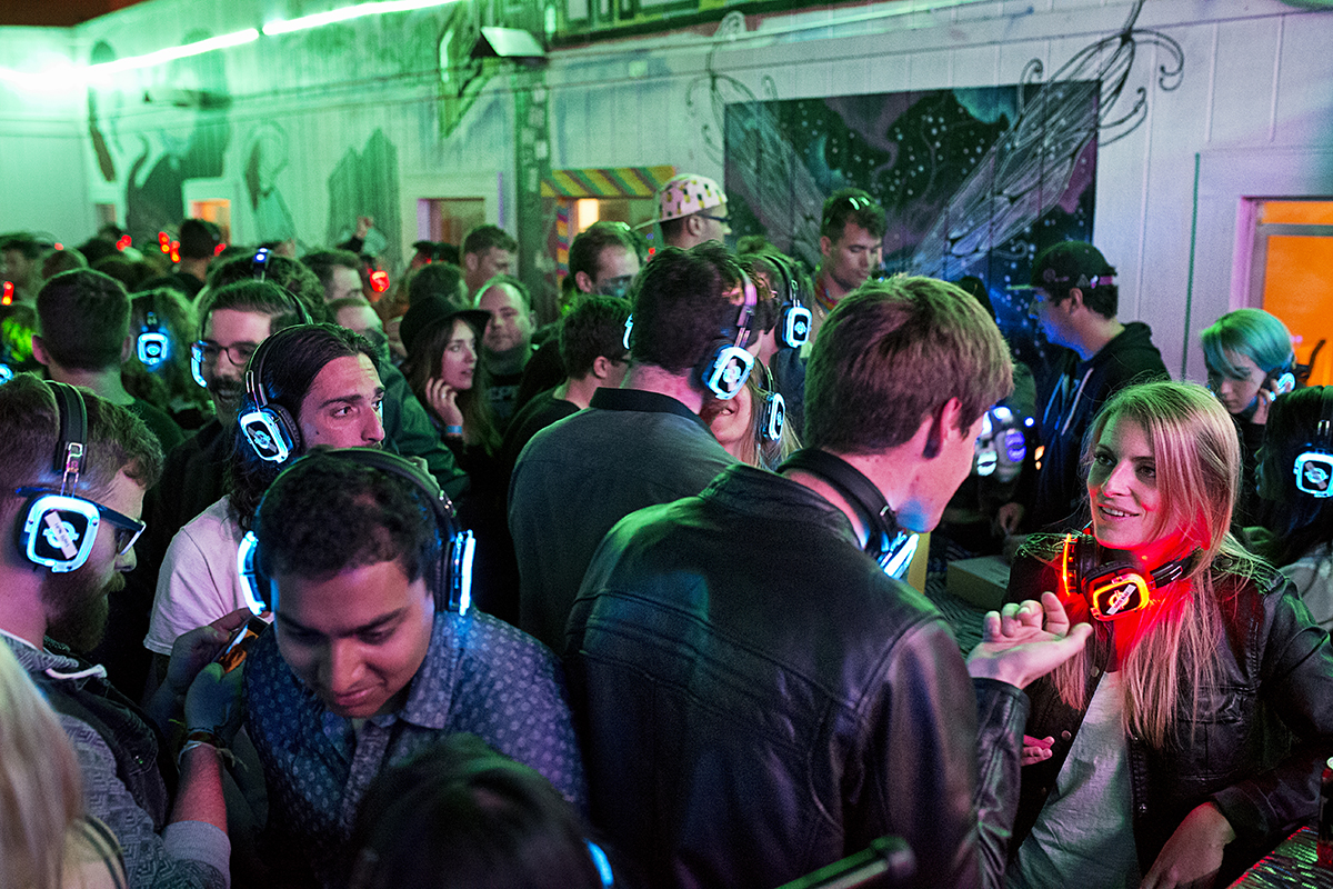 Guests of a party to celebrate the three-year anniversary of 20 Mission, a co-living house, dance and listen to a DJ playing music using silent disco headphones in the building's courtyard during the party in San Francisco, Calif., on Saturday, March 28, 2015. Around 40 people live in the building, which is a former single room occupancy hotel that had been vacant for several years before being turned into the co-living space. Many residents are start-up entrepreneurs and the community is a mix of temporary occupants and people who have made the space their home on a more long-term basis.
