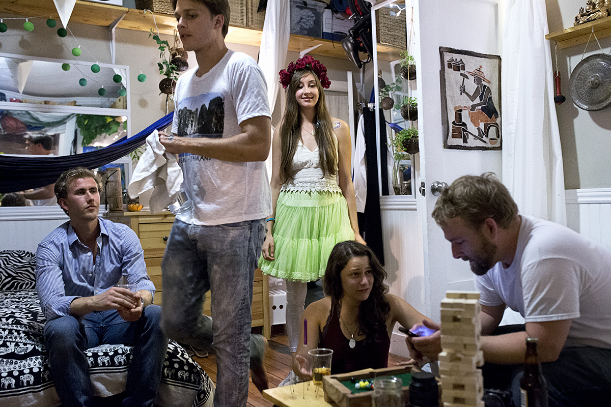 Emily Erickson (center) and her boyfriend Sean Ahrens (second from left) host guests in their room at 20 Mission, a co-living space, during a party to celebrate the community's three-year anniversary in San Francisco, Calif., on Saturday, March 28, 2015. Around 40 people live in the building, which is a former single room occupancy hotel that had been vacant for several years before being turned into the co-living space. Ahrens and many of the other residents are start-up entrepreneurs and the community is a mix of temporary occupants and people who have made the space their home on a more long-term basis.