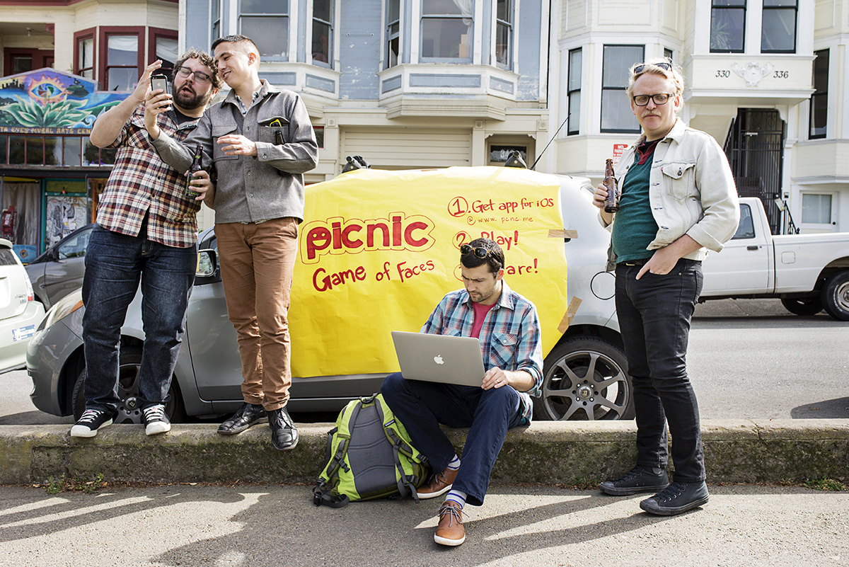 Andrew Hines (center) works on trying fix a problem during a beta launch party for his app Picnic with his co-founder Cassidy Clawson (second from right) at Precita Park in San Francisco, Calif., on Sunday, March 22, 2015.  Picnic is a game that involves taking selfie photos in response to challenges to act out certain emotions.  The launch had to be postponed after the co-founders realized the app wasn't working because Apple's TestFlight program, which was necessary for the beta testing, was down and not working that day.