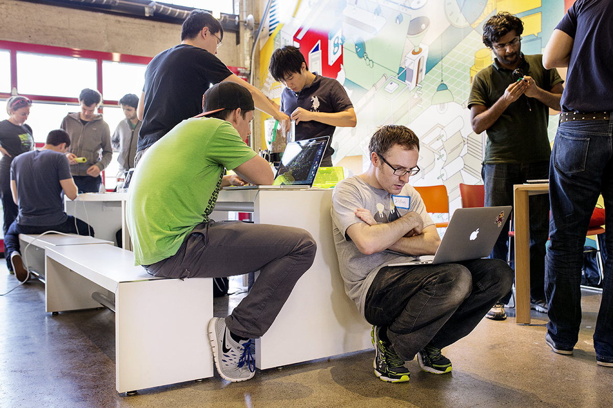 Jonathan Dillon (center) works with his teammates on making a pet food dispendser that could be controlled remotely while participating in the Hackster Hardware Weekend hackathon at the PCH Innovation Lab in San Francisco, Calif., on Sunday, March 15, 2015.  The hackathon, organized by Hackster.io, featured hardware challenges including one to create a hack for the DeLorean car.  Hackathons are events usually lasting a few days in which computer programmers and others involved in software and hardware development collaborate on a project over a set period of time, often while competing for awards and prizes.