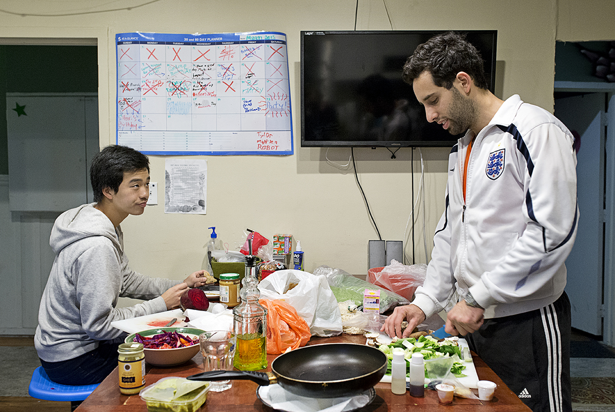 Lior Neu-ner (right) cooks while his housemate Darren Lee eats dinner in the communal kitchen at 20 Mission, a co-living house, in San Francisco, Calif., on Monday, March 23, 2015.  Around 40 people live in the building, which is a former single room occupancy hotel that had been vacant for several years before being turned into the co-living space.  Many of the residents are start-up entrepreneurs and the community is a mix of temporary occupants with people who have made the space their home on a more long-term basis.  Neu-ner was living at 20 Mission for a few months while in San Francisco to participate in a start-up accelerator with his parking app Parko and Lee lived in the house temporarily while transitioning to the city.
