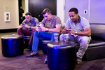 Danny Lizotte, Tim Lizotte and Colton Walker (left to right) check their phones while attending the Startup and Tech Mixer in support of a friend who was launching a job app at the event in San Francisco, Calif., on Friday, August 8, 2014.  The networking event is held once ever few months and draws hundreds of attendees.