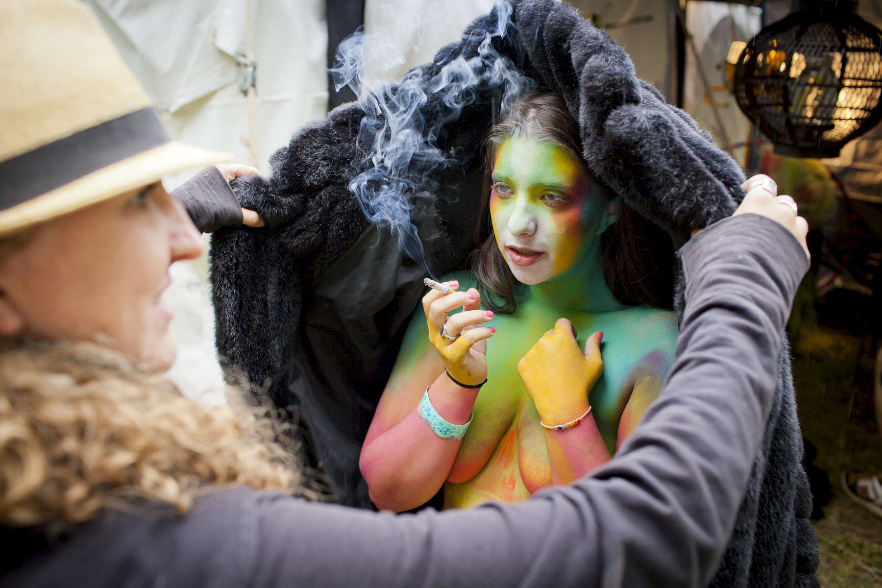 A young woman smokes a cigarette after having body painting done, at Liberate Festival in Sheldon. by Vermont photographer Judd Lamphere