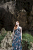Young woman  stands in a cave in Thailand. by Vermont photographer Judd Lamphere