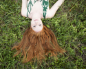 Redhead Shannon lying in the grass at All Souls in Shelburne, by Vermont photographer Judd Lamphere