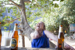Young woman laughing with beer bottles on the beach in Thailand. by Vermont photographer Judd Lamphere