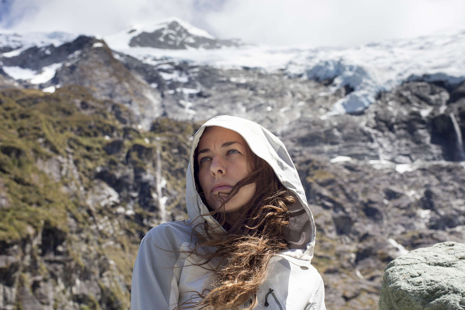 Young woman stands in front of a glacier in New Zealand. by Vermont photographer Judd Lamphere