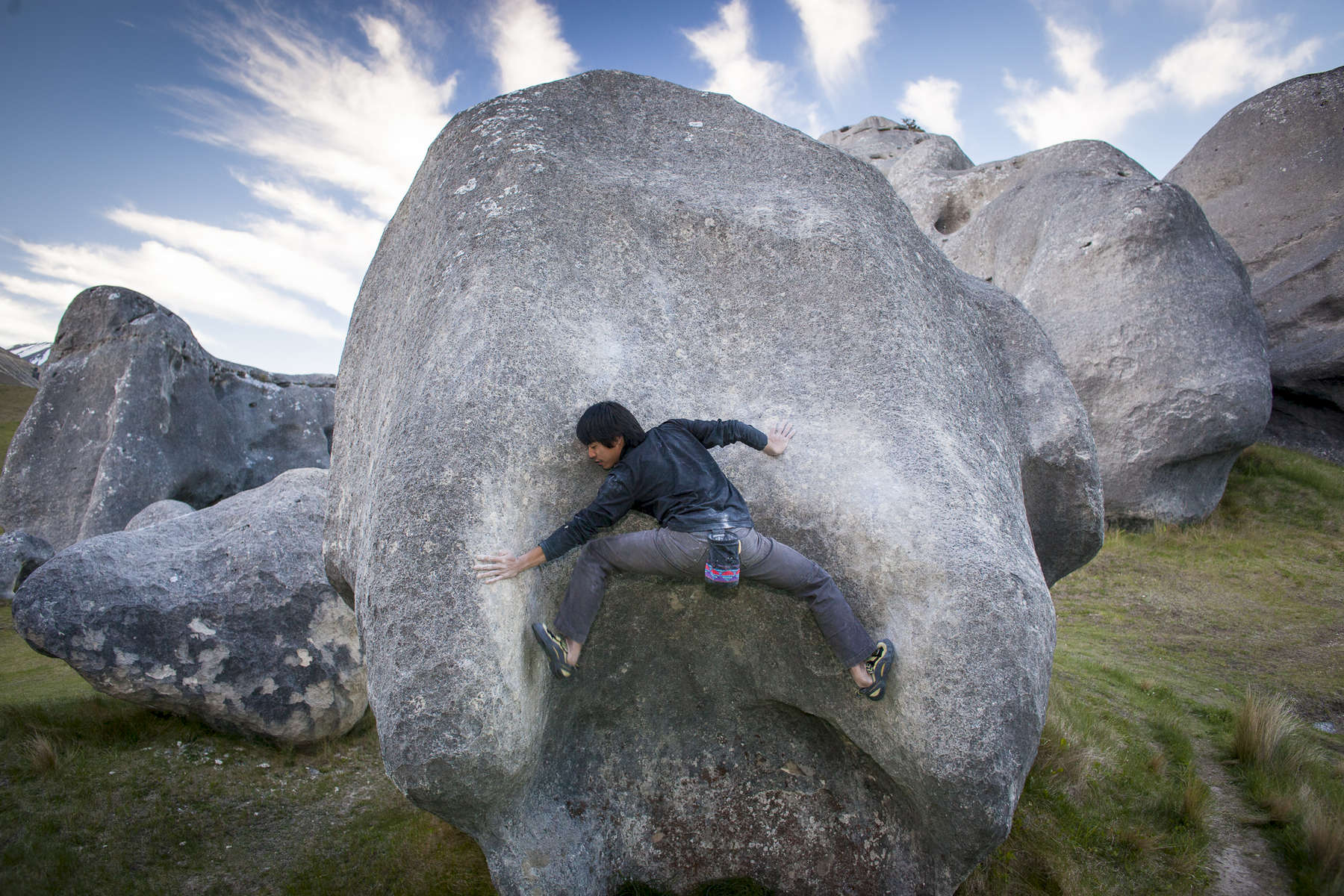 Woman hiker on rocks at Arthurs Pass, New Zealand, a destination rock climing and bouldering spot. by Vermont photographer Judd Lamphere